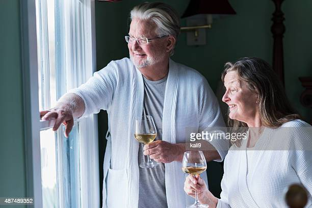 Senior couple in bedroom drinking, looking out window