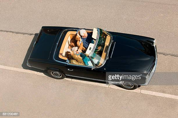 Senior couple in convertible car driving down street, elevated view