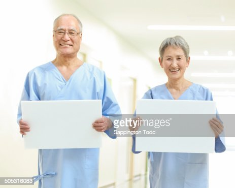 Senior Couple In Examination Gown Holding Placard