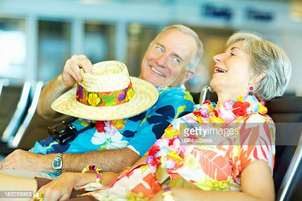 Senior couple in floral clothing waiting at an airport lounge