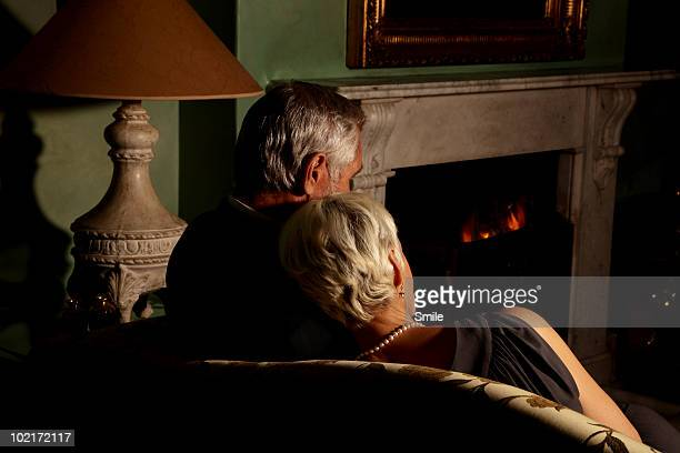 Senior couple in front of fireplace, from behind