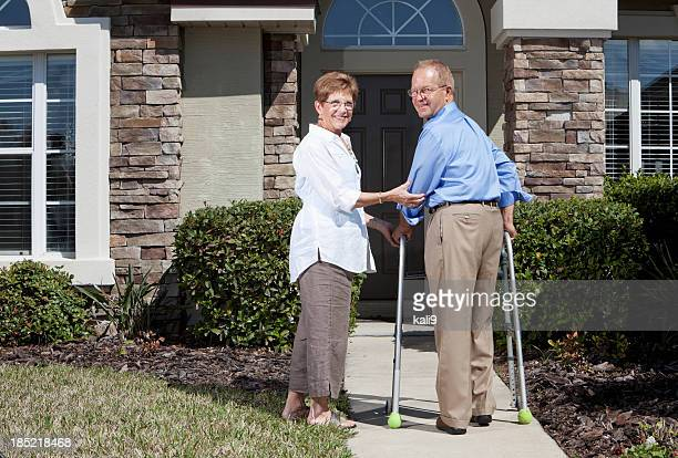 Senior couple in front of house, using walker