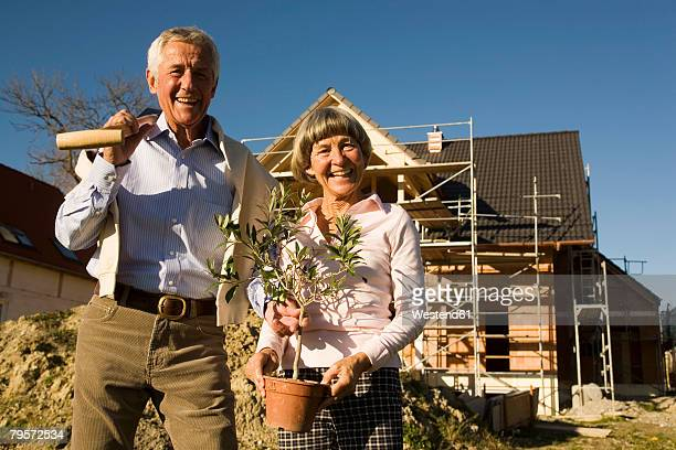 Senior couple in front of partially built house