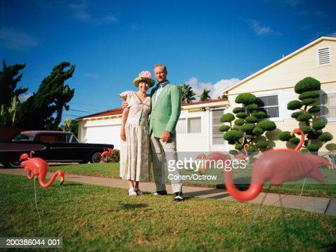 Senior couple in front of their home with toy flamingoes : Stock Photo