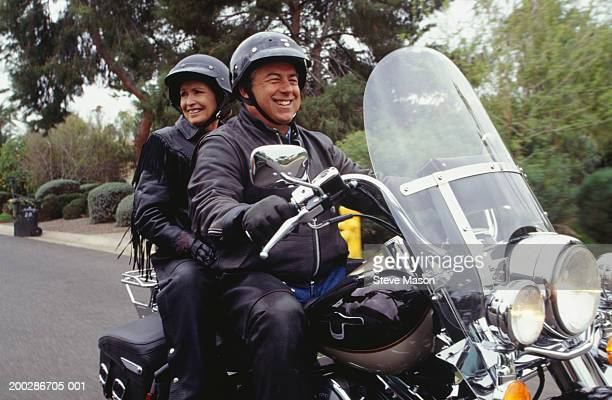 Senior couple in leather jackets riding motorcycle