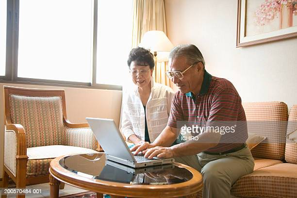 Senior couple in living room using laptop