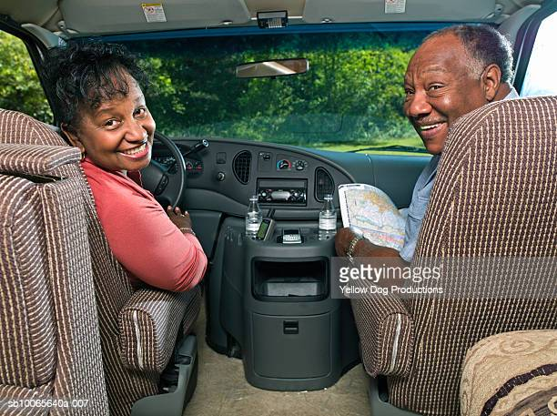 Senior couple in motorhome, man holding map, smiling, portrait