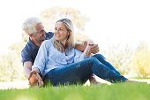 Senior couple sitting in park. Happy smiling couple sitting on grass. Portrait of a senior man and woman relaxing at park and looking at each other.