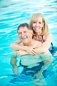 Cute senior couple smiling in swimming pool together