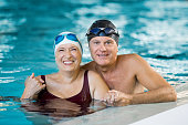 Portrait of a senior couple bathing in swimming pool and looking at camera. Smiling mature man and old woman enjoying time together in a swimming pool. Happy retired couple after aqua fitness.