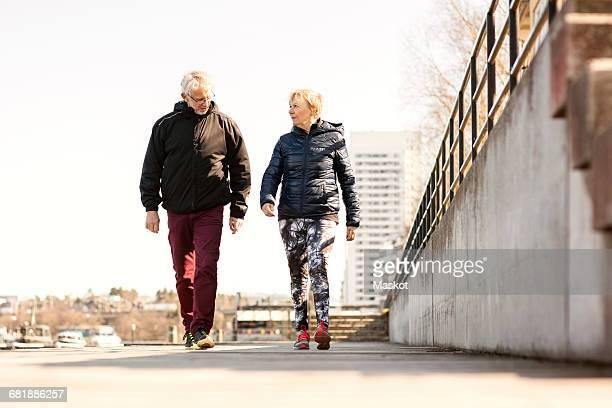 Senior couple in sportswear walking on sidewalk against clear sky