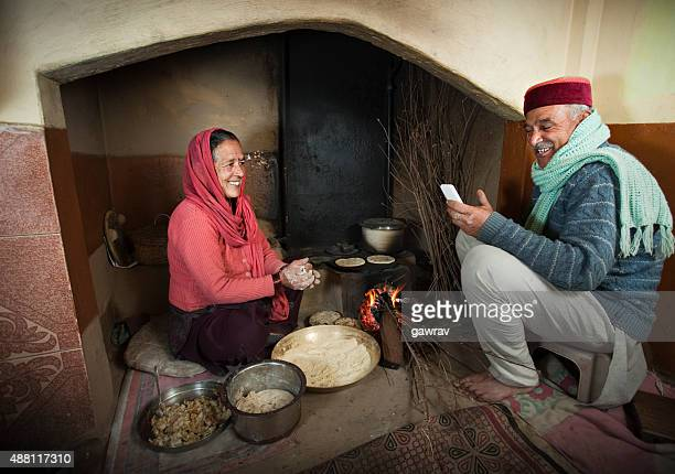 Senior couple in traditional kitchen of rural Himachal Pradesh India.