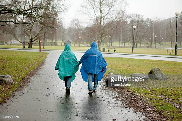 Senior couple in waterproof clothing walking through park