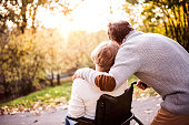 Senior couple in autumn nature. Man and woman in a wheelchair on a walk.