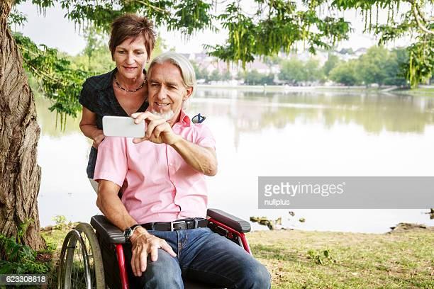 Seniorenpaar im Rollstuhl, die selfies