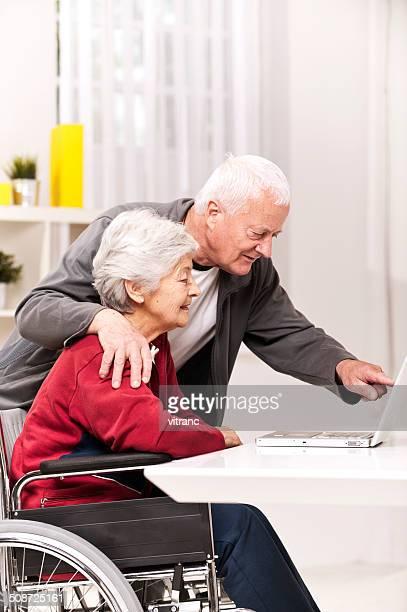 Altes Paar im Rollstuhl mit laptop