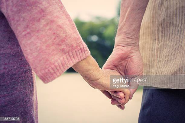 A senior couple is holding hands