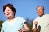 Senior couple jogging in the sun
