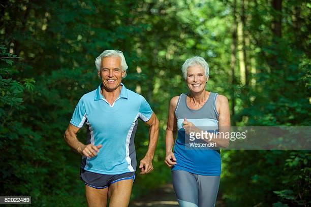 Senior couple jogging, smiling, portrait