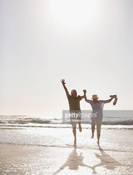 Senior couple jumping on beach