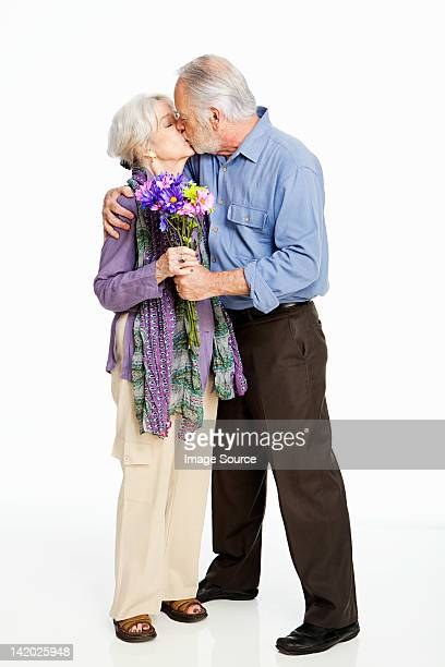 Senior couple kissing against white background