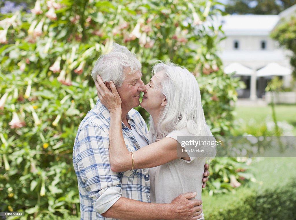 Senior couple kissing in garden : Stock Photo