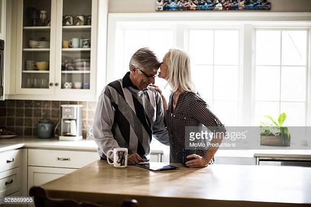Senior couple kissing in kitchen