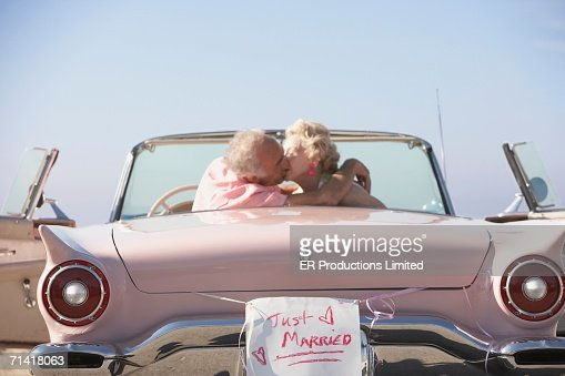Senior couple kissing in pink convertible with Just Married sign