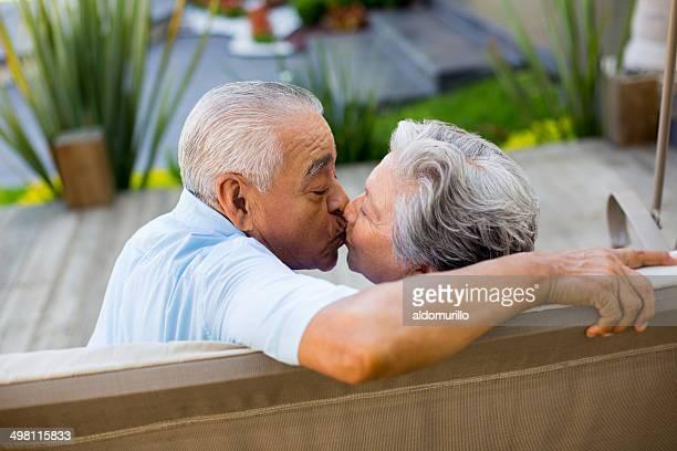 Altes Paar Küssen auf einer Bank