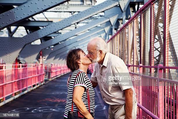Senior couple kissing on bridge