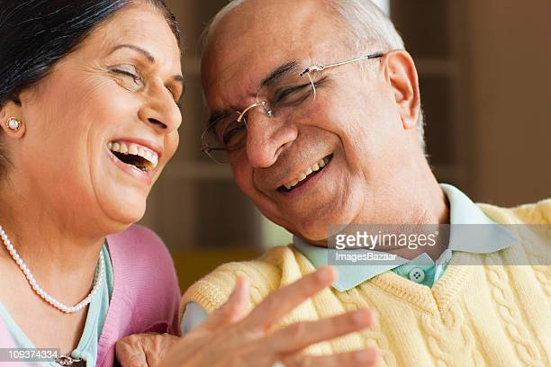 Senior couple laughing, indoors