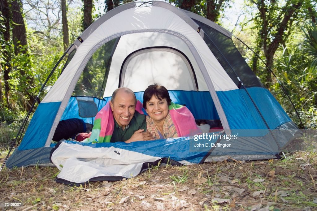 Senior couple laying in tent smiling : Stock Photo