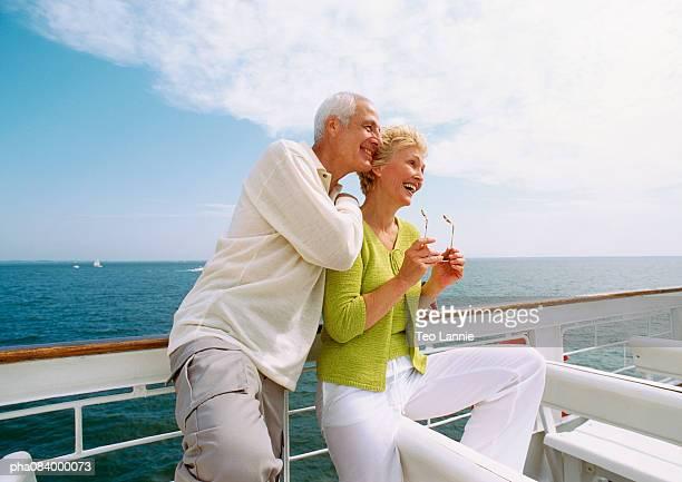 Senior couple leaning on railing, smiling.