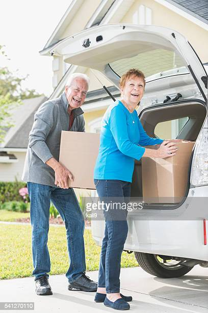 Senior couple loading or unloading boxes from car trunk