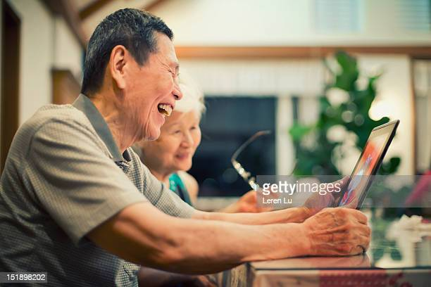 Senior couple look at photos on tablet happily