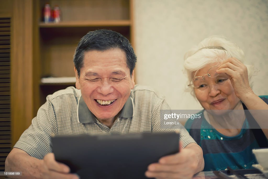 Senior couple look at tablet happily : Stock Photo