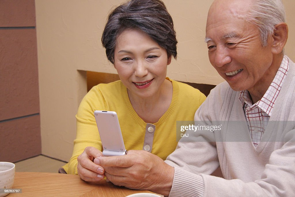 Senior couple looking at a mobile phone, smiling : Unknown