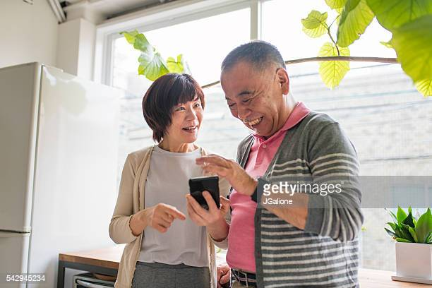 Senior couple looking at a smartphone laughing