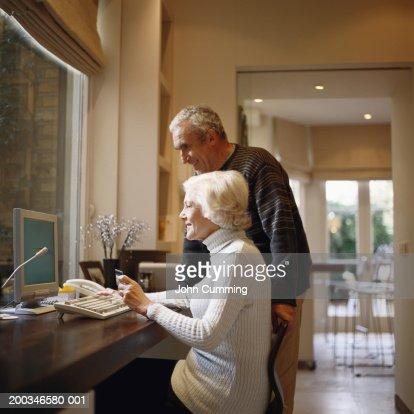Senior couple looking at computer, woman holding credit card : Stock Photo
