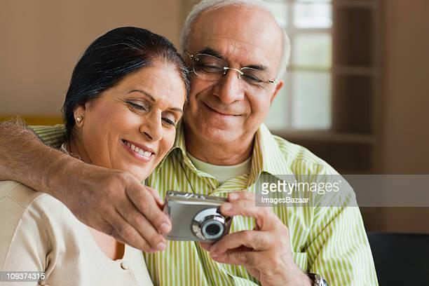 Senior couple looking at digital camera indoors