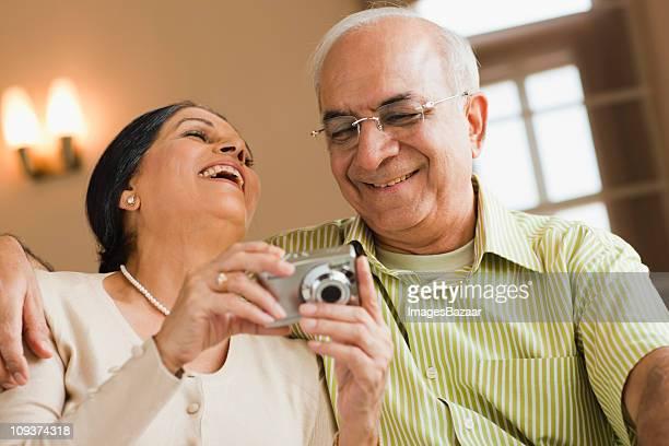 Senior couple looking at digital camera, laughing