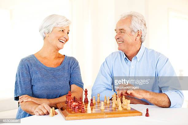 Senior Couple Looking At Each Other While Playing Chess
