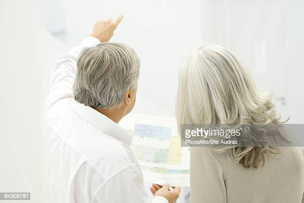 Senior couple looking at floor plans, rear view