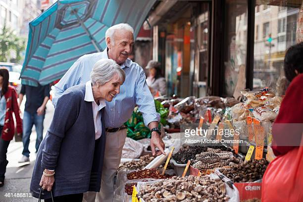 Senior couple looking at food on street in city