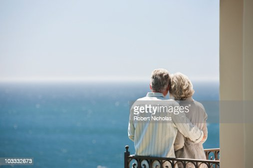 Senior couple looking at ocean view from balcony : Stock Photo