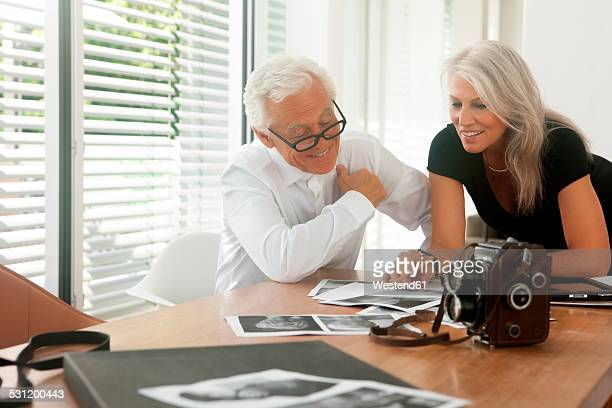 Senior couple looking at photographs lying on a table