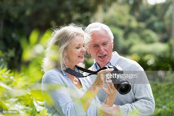 Senior couple looking at photos taken on camera