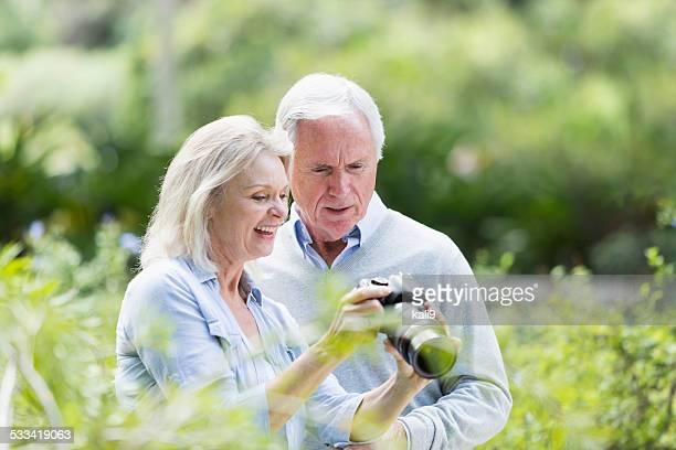 Senior pareja mirando fotos tomadas con una cámara