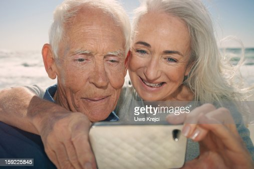 Senior couple looking at smart phone : Stock Photo