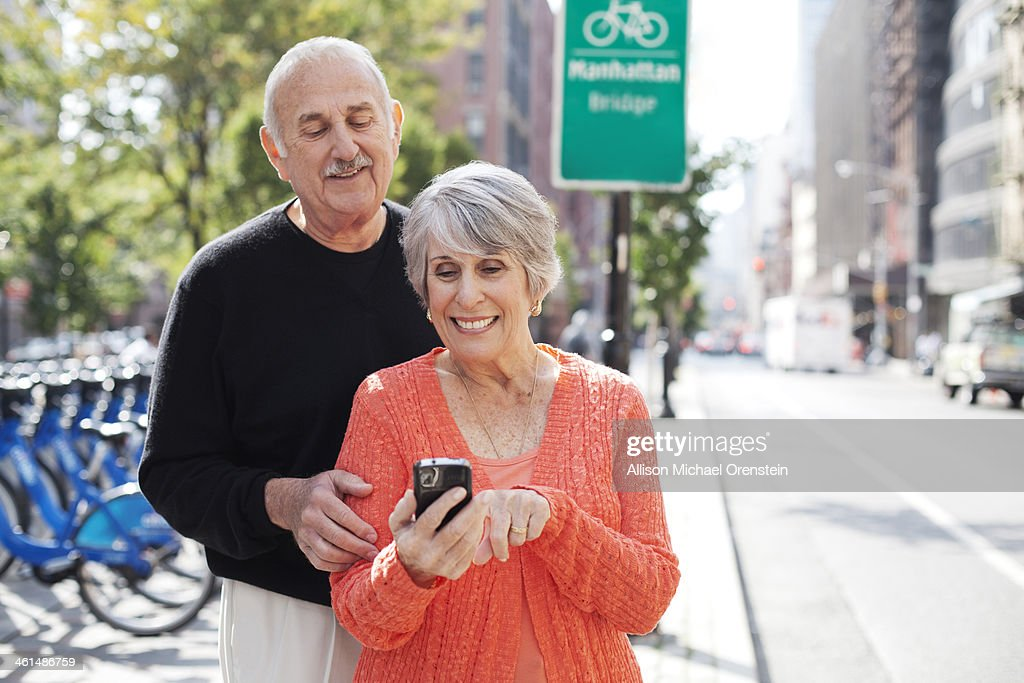 Senior couple looking at smartphone in city : Stock Photo